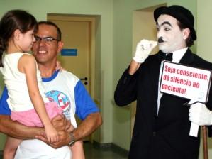 """""""Chaplin"""" brinca com pai e filha, alertando para a importância do silêncio no hospital.  (Foto: Divulgação/Códgio BR Comunicação)"""